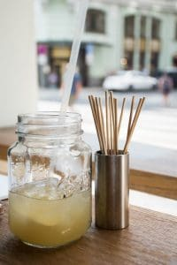 Half glass full ginger soda made in-house and skewer container at Spejle Restaurant in Prague